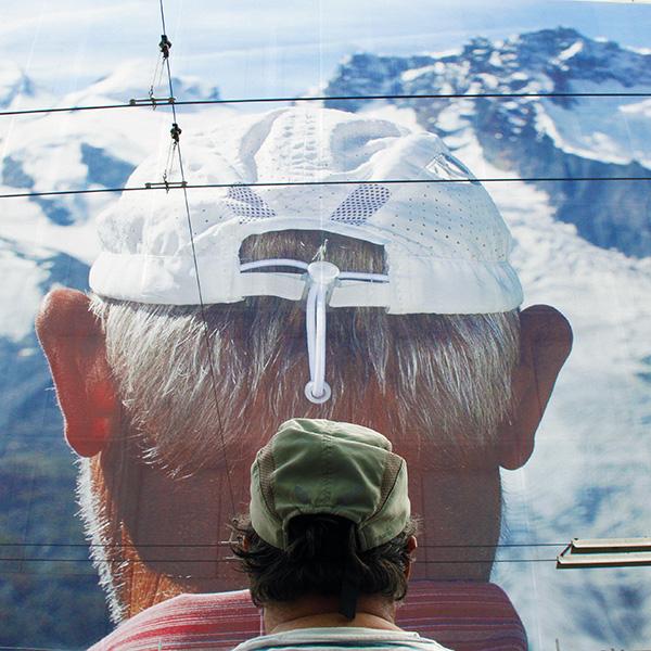 Un portrait géant de Martin Parr réalisé à Zermatt (et ici mis en abyme avec Philippe, modèle d'un jour) occupe la façade entière de la banque cantonale vaudoise. Photo : Pascal Kober.